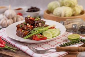 cerdo dulce con cebolletas picadas, ají, lima, pepino, tomate y ajo