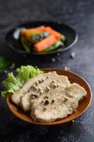 Grilled chicken breast sprinkled with pepper and placed on a wooden plate photo