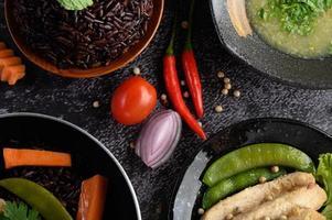 Platos variados de verduras, carnes y pescados sobre un fondo de piedra negra