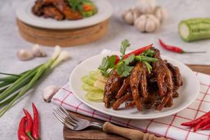 Sweet fried chicken feet with coriander, chili, cucumber and tomato photo