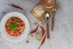 Thai papaya salad on a white plate with sticky rice, chili, spoon and fork