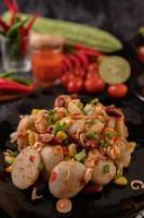 Ensalada picante de albóndigas con chile, limón, ajo y tomate foto