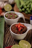 Red eye chili paste with lemon and chili on wooden board