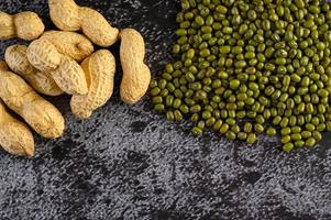 Peanuts and mung beans on a black cement floor background