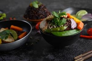 Purple rice berries with beans, carrot and mint leaves in a bowl