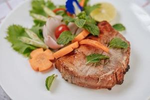 Pork steak with tomato, carrot, red onion, peppermint, butterfly pea flower and lime photo