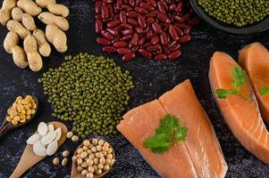 Legumes with salmon on a black cement background photo