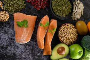 Legumes, fruit, and salmon on a black cement background photo