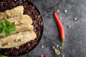 Pechuga de pollo a la parrilla con pimientos sobre bayas maduras de arroz púrpura