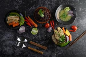 Assorted dishes of vegetables, meat and fish on a black stone background