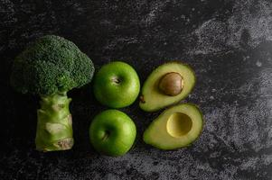 Broccoli, apple and avocado on a black cement floor background