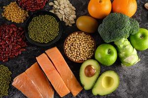 Legumes, broccoli, fruit, and salmon on a black cement background