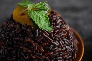 Purple rice berries cooked in a wooden dish with mint leaves and pumpkin