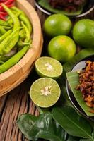Limes cut in half and chilis on wooden surface