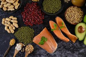 Legumes, fruit, and salmon on a black cement background