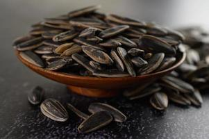 Sunflower seeds in a wooden bowl on black surface