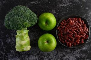 Broccoli, apple and beans on a black cement floor background