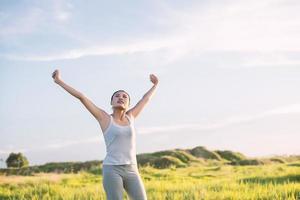 Feliz hermosa mujer con los brazos estirados en una pradera foto