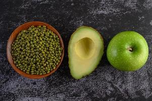 Mung bean, avocado and apple on a black cement floor background