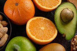 Rebanada de primer plano brillante de naranja fresca, manzana, kiwi y aguacate
