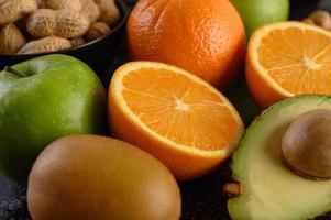 Rebanada de primer plano brillante de naranja fresca, manzana, kiwi y aguacate foto