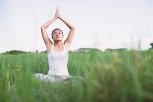 Young woman in yoga pose practicing meditation in the meadows