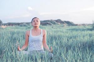 Yoga woman In the lotus posture in a sunny meadow photo