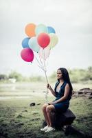 Young woman holding colorful balloons in nature