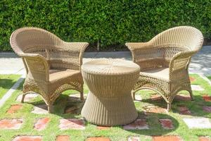 Wicker lounge chairs and table by hedge
