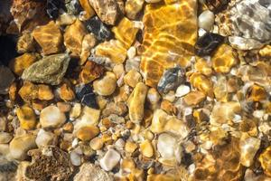 Colorful pebbles under water for background