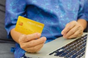 mujer de la tercera edad sosteniendo una tarjeta de crédito foto