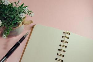 cuaderno y bolígrafo en escritorio rosa foto