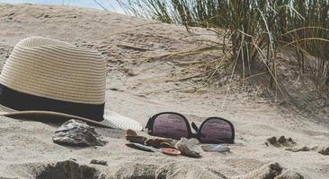 Sunglasses and hat on beach photo