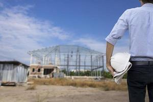 Engineer holding a white hard hat while looking at construction site