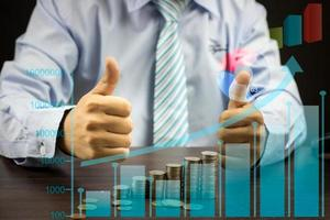 Business man holding thumbs up with a graph photo
