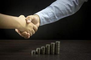dos personas dándose la mano con una pila de monedas sobre la mesa