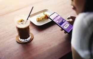 persona que usa el pago con teléfono móvil en un café
