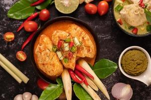 Chicken curry in a bowl with lemongrass lime, tomatoes and garlic photo