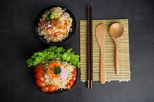 Bowls of noodles with ingredients and chopsticks, wood spoon