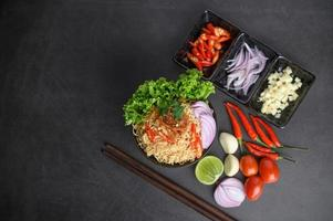Bowls of noodles with ingredients and chopsticks