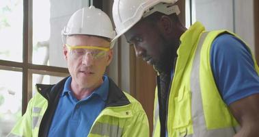 equipe diversificada de engenheiros discutindo relatório no tablet video
