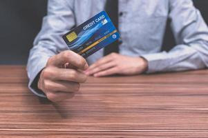 hombre sosteniendo una tarjeta de crédito azul
