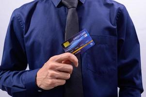 Man wearing a blue shirt holding a blue credit card