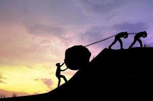 silueta de hombres arrastrando una roca por un acantilado
