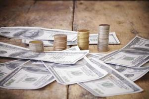 Coins and money on a wooden table photo
