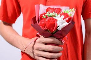 Person wearing red holding flowers
