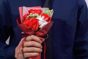 Person holding a bouquet wearing a suit