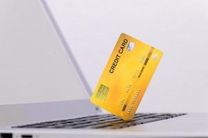tarjeta de crédito amarilla en la computadora foto