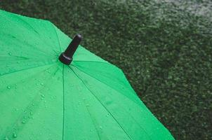 Green umbrella with rain drops