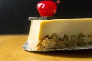 Slice of cheesecake with chocolate and cherry on wood table